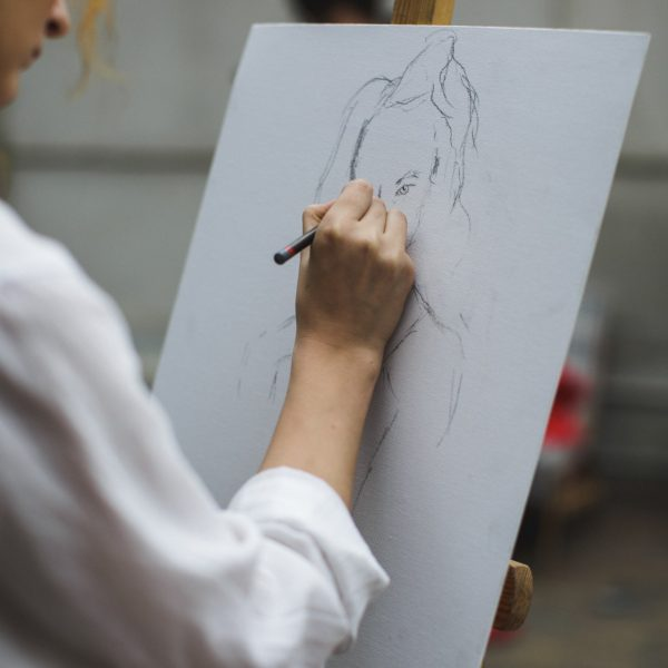 woman-in-white-long-sleeve-shirt-drawing-on-paper-3778179